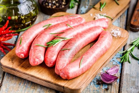 Raw homemade sausages on cutting board with rosema...