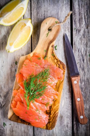 Slices of smoked salmon on a wooden chopping board...