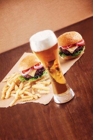 Photo pour Un verre de bière avec un cheeseburger et des frites en arrière-plan. L'accent est mis sur Burger . - image libre de droit