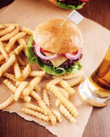 Photo pour Cheeseburger and Fries avec un verre de bière en arrière-plan. L'accent est mis sur Burger . - image libre de droit