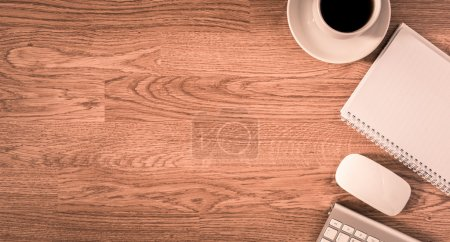Office table with notepad, computer and coffee cup and computer