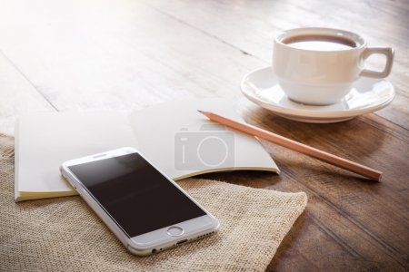 Photo for Cup of coffee on a wooden table with glass of water on the Sackcloth bags and smartphone and notebook and pencil. Simple workspace or coffee break with web surfing - Royalty Free Image