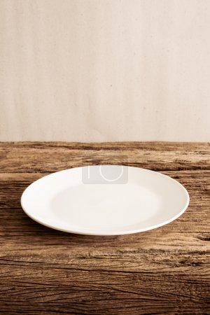 Photo for Empty Plate on wooden tabletop against grunge wall. vintage tone - Royalty Free Image