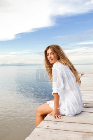Portrait of Young smiling woman in white clothes o...