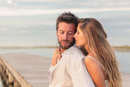 Photo pour Portrait d'une femme embrassant son homme par derrière sur fond de mer - image libre de droit