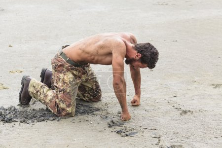 Kneeling Shirtless Soldier with Fists on Ground