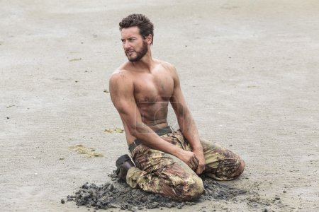 Photo for Muscled Shirtless Soldier in Camouflage Pants and Black Shoes Kneeling on the Beach Sand - Royalty Free Image