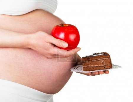Pregnant woman holding an apple and  piece  cake  on white.