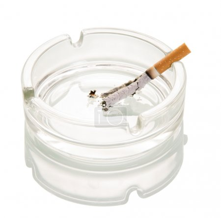 Decaying cigarette in  glass ashtray isolated on white background.