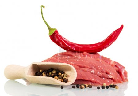 Raw meat beef, red and black pepper isolated on white.