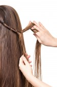 Hairdresser braids long straight brown hair isolated on white.