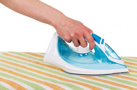 Photo for Steam iron in a female hand, ironing towels on a white background. - Royalty Free Image