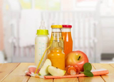 Photo for Bottles with milk and juice, fruit puree Bank, apples, spoon and soother on the background of the kitchen. - Royalty Free Image
