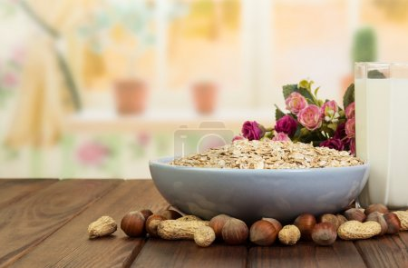Bowl  oatmeal,  glass  milk and nuts on  background the kitchen.