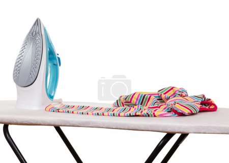 Steam iron, ironing board and clothes isolated on white.