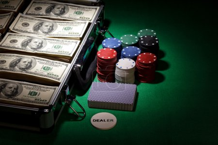 Photo pour Poker chips and dollar bills in case on green background - image libre de droit