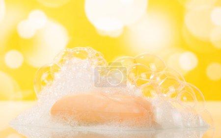 Photo pour Savon bar et bulles sur fond jaune - image libre de droit