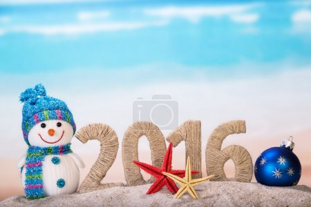 Photo for New year sign with starfishes on sandy beach and snowman - Royalty Free Image