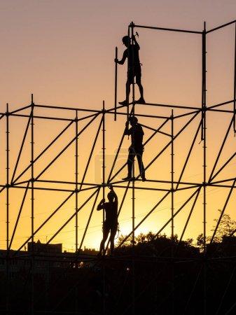 Les constructeurs sont en train de démonter la structure tubulaire. Sur fond de ciel couchant, seules des silhouettes sont visibles. Les travailleurs tiennent des outils et des tuyaux.
