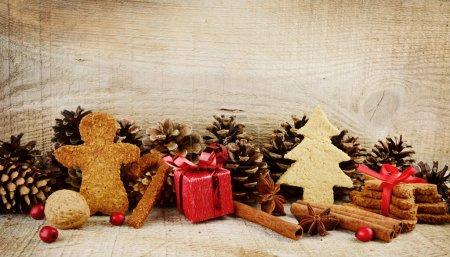 Photo pour Biscuits divers de pain d'épice de Noel avec le cadeau rouge, arbre de Noel, claus de santa, scène de bâton sur la surface en bois - image libre de droit