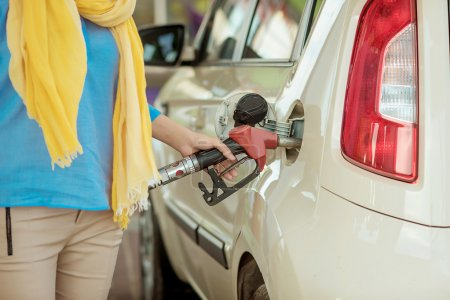 girl pumping diesel in to the tank. car fill with gaon pump. soline at a gas station. Gas stati