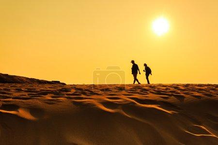 Two people walking on sand desert...