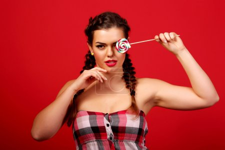 Beauty fashion model girl eating colorful lollipop. Surprised funny young woman with braids hairstyle, nails and makeup beige, isolated on a red background
