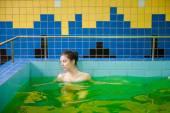 Žena v bazénu se zelenou vodou