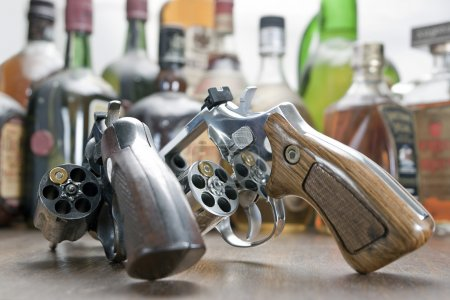 Photo for Two weapons with only one bullet each. At the bottom a few bottles of whiskey. Concept of challenge and test of courage. - Royalty Free Image