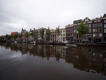 Photo pour Architecture typique de style Amsterdam façade extérieure reflet de maisons bâtiments dans le canal d'Amstel en Hollande Pays-Bas - image libre de droit