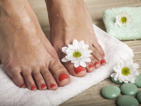 Photo pour Pieds féminins avec des gouttes d'eau, serviette, fleurs et rochers de spa. - image libre de droit