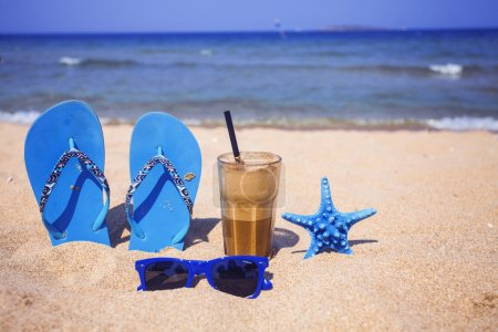 Photo for Iced coffee, blue flip-flops, starfish and sunglasses on a sandy beach - Royalty Free Image