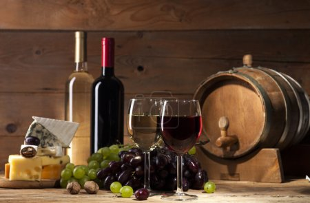 Wine with various types of cheese on wooden background