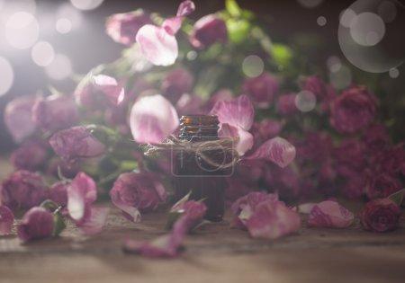 Photo pour Gros plan de bouteille d'huile essentielle de rose avec des feuilles tombantes sur fond en bois. Avec effet d'éclairage spécial bokeh . - image libre de droit