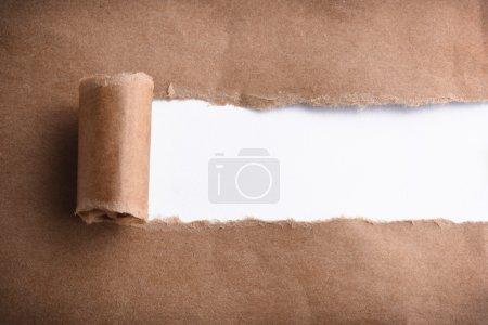 Photo pour Papier brun déchiré pour révéler le panneau blanc - image libre de droit