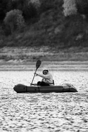 Photo for Swim in Packraft. Packraft, one-person light raft used for expedition or adventure racing, on a lake, inflatable boat Ride on a mountain lake. - Royalty Free Image