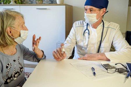Photo pour Le médecin aidant aide une grand-mère âgée négative de 85 ans, une patiente à la maison ou à l'hôpital. Le concept de soins de santé pour les personnes âgées. Refus de vaccination - image libre de droit