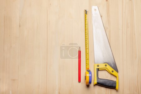 woodworkers tools - ruler, saw, pencil on wooden table