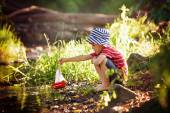 Cute little toddler boy, playing with wooden boat on a pond