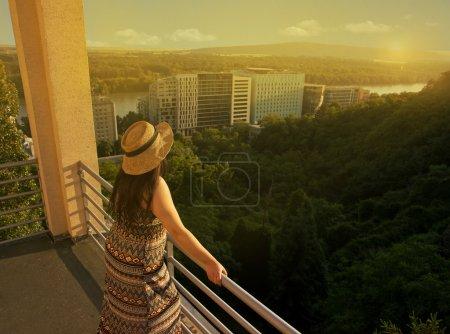 Photo pour Femme debout au balcon au coucher du soleil et la recherche à Distance - image libre de droit