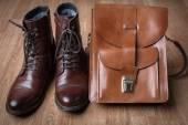 Pánské boty a hnědou tašku na dřevěný stůl