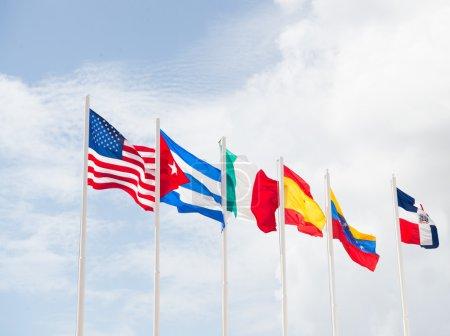 Photo pour De nombreux drapeaux nationaux coloré de différents pays sur les mâts extérieurs sur fond bleu ciel nuageux, symboles des Etats-Unis cuba Irlande Espagne venezuela et République dominicaine - image libre de droit