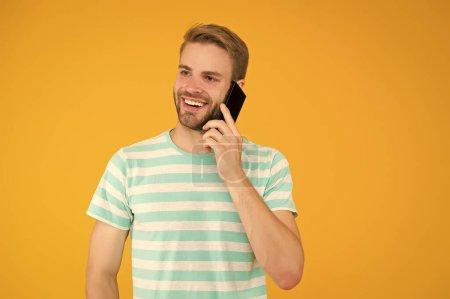 Importance d'être communicatif. Happy man parler sur téléphone portable fond jaune. Communication verbale. Communication mobile. Communication téléphonique. Technologies de communication. La vie moderne