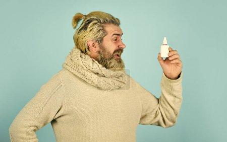 Helpful nasal spray. man use nasal drops during co...
