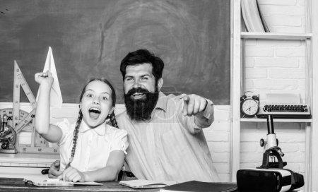 Photo pour Un vrai bonheur. journée de la connaissance. Enseignement à domicile. petite fille enfant avec barbu professeur homme dans la salle de classe. leçon privée. retour à l'école. Enseignement privé. fille étudier avec le père. Journée des enseignants. - image libre de droit
