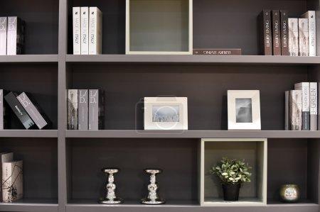 Photo pour Étagères foncées modernes avec des livres et des cadres de photo - image libre de droit