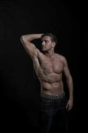 Photo pour Young sexy handsome athletic man with naked torso on dark background, side view - image libre de droit