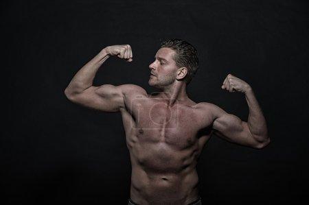 Photo pour Sexy jeune bel homme athlétique avec torse nu sur fond sombre, vue de face - image libre de droit