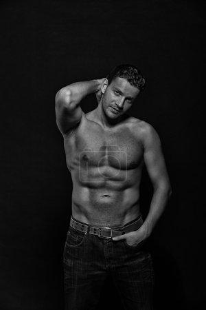 Photo pour Sexy jeune bel homme athlétique avec torse nu sur fond sombre avec fond - image libre de droit