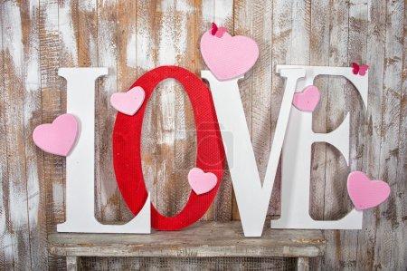 Photo pour Mot d'amour avec des coeurs roses sur les lettres blanches et rouges sur fond de planches de bois - image libre de droit